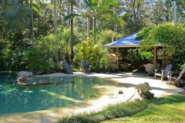 Palms and grasses are low maintenance plantings by the pool.