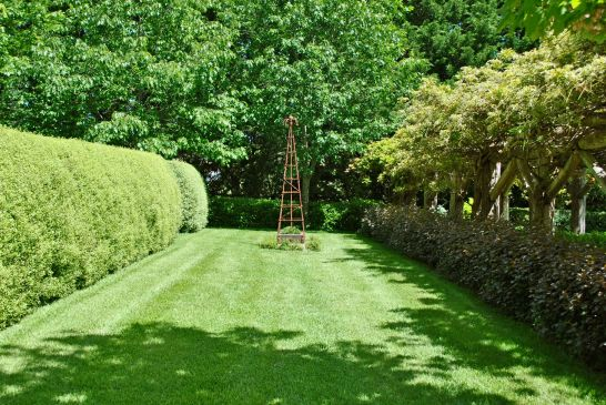 One of many long views: between the wisteria pergola and an adjacent hedge the focal point is a metal obelisk.