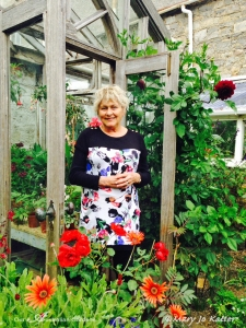 Helen in her elegant and simple potting shed/green house where plants wait for their turn in the garden.