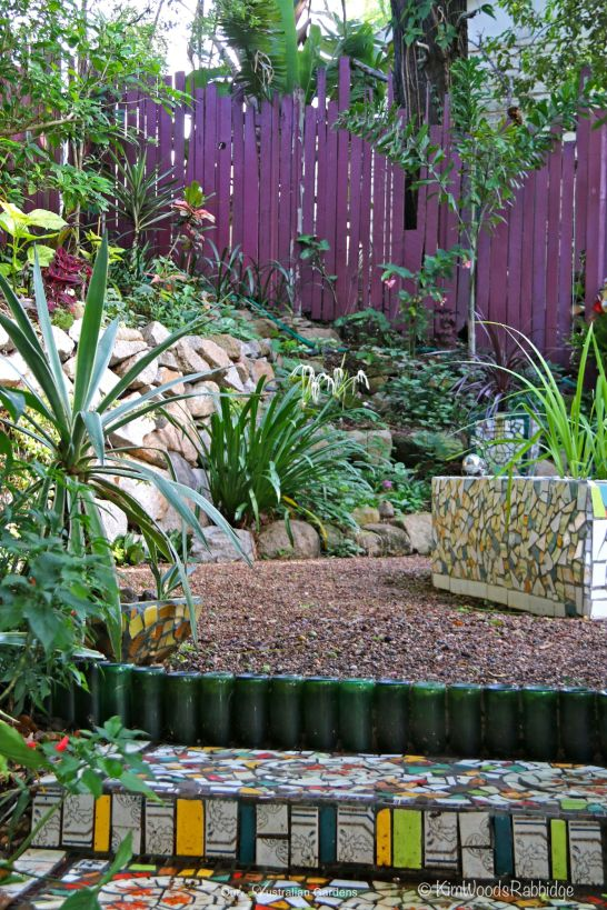 A wiggly purple painted fence is the garden's backdrop.