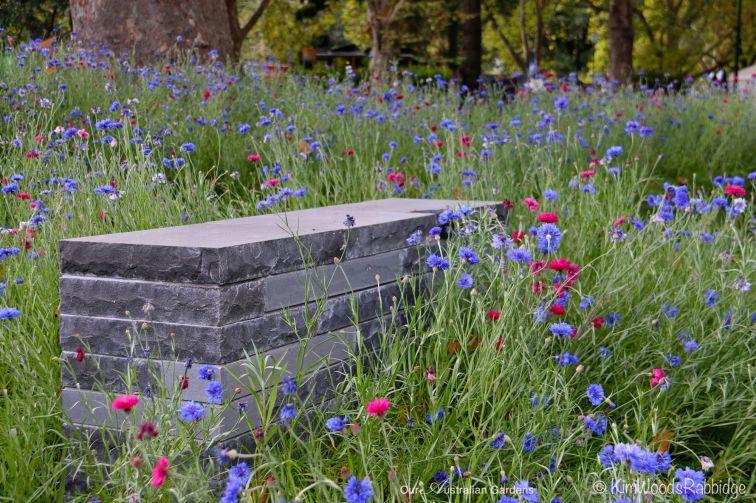 Stacked bluestone bench set amongst soft plantings.