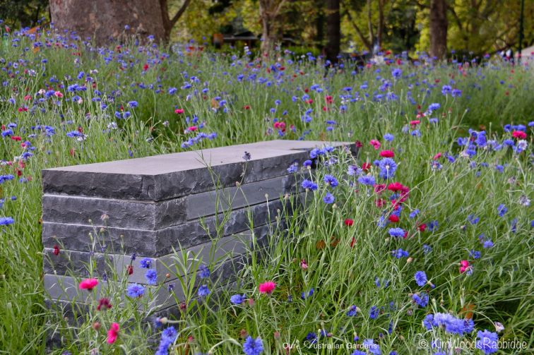 Stacked bluestone bench set amongst soft plantings.